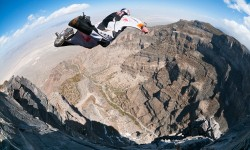 Red Bull Air Force Team members BASE jumping off a huge cliff in southwestern Utah in wing suits.